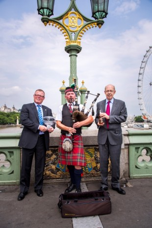 Tony Hunt and Peter Mielzynski from The Innis & Gunn Brewing on Westminster Bridge with a bagpiper