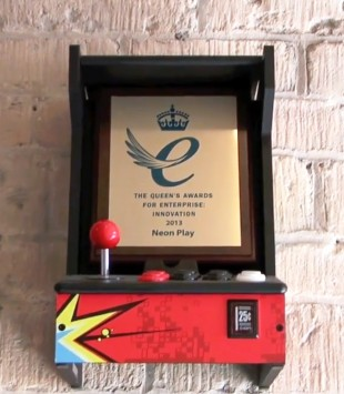 The Queen's Award won by Neon Play displayed in an arcade machine frame