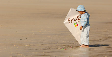 A toddler on a beach holding a kite featuring the frugi brand.