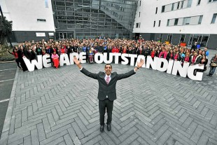 Walsall students standing behind a sign saying 'We are outstanding'