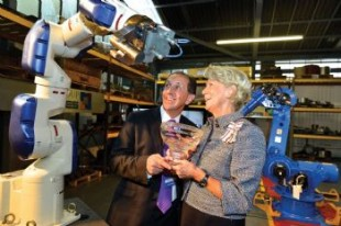 Ingrid Roscoe and Mark Ridgway standing beside a robotic arm.
