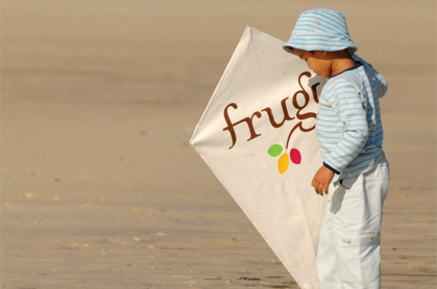 A toddler on a beach holding a kite featuring the frugi brand