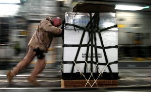 Man pushing cargo action photo. Handle with care.