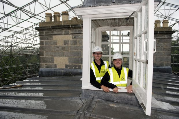 2 men in hard hats on the roof of a historic building.