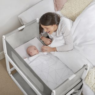 Mum comforting baby in a bedside crib.