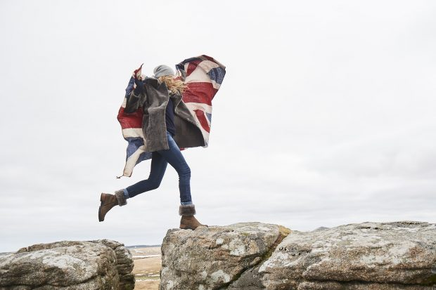 Woman jumping between 2 rocks carrying a Union Flag.