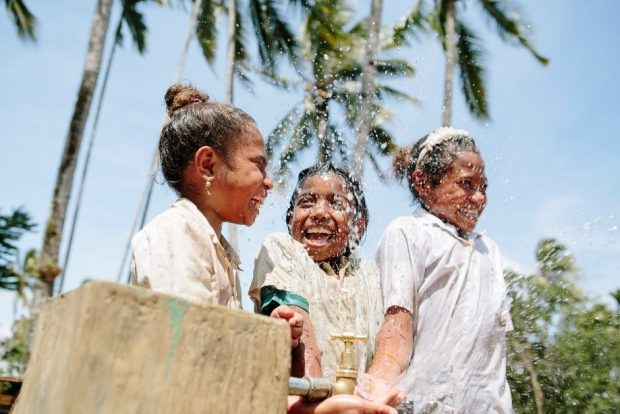 3 girls in Timor Leste playing with water from a tap.